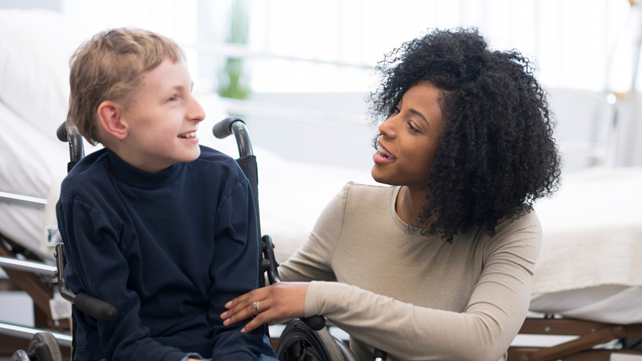 Boy in wheel chair smiling with adult carer