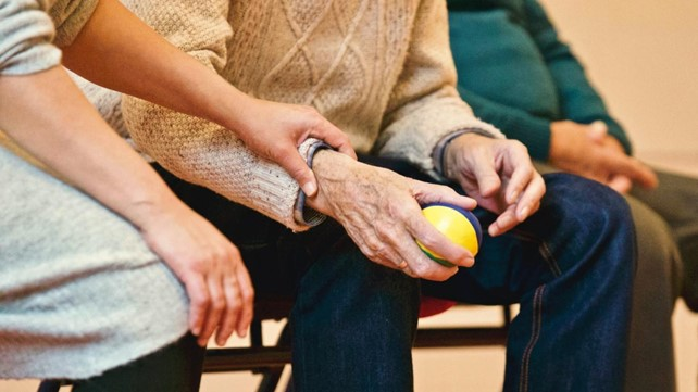 Senior man squeezing ball with female carer checking pulse