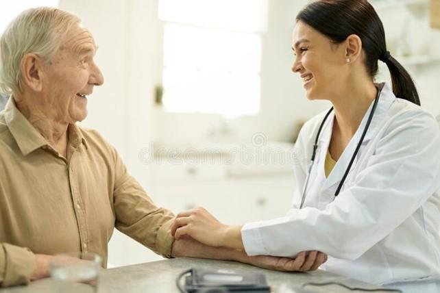 Friendly nurse helping elderly man lift sleeve to receive injection