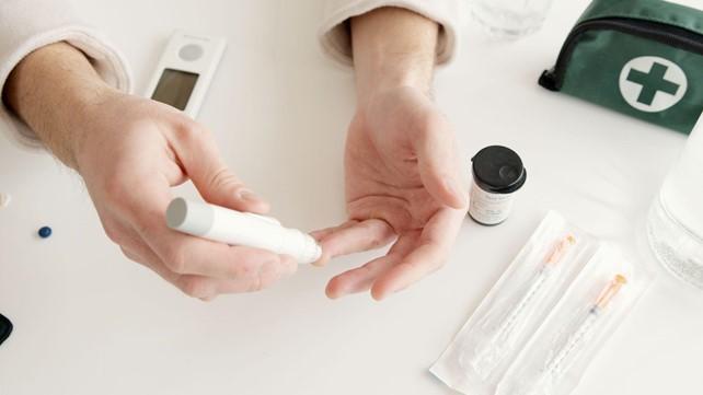Person pricking finger testing insulin